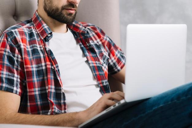 Crop man using laptop