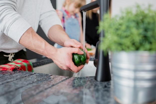Crop man washing pepper