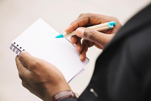 Crop man writing in blank notebook
