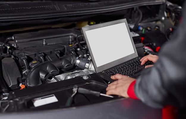 Механик с помощью ноутбука во время ремонта автомобиля