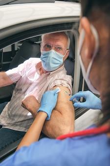 Медик вводит вакцину в руку старшего водителя