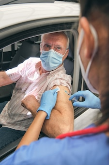 Crop medic injecting vaccine into arm of senior driver