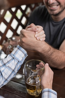 Crop men arm wrestling in bar