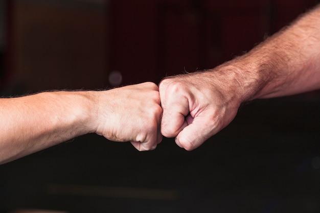 Crop men bumping fists