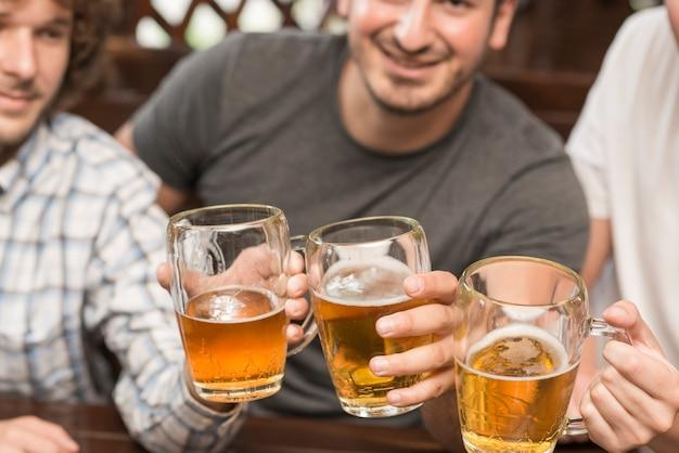 Crop men clinking mugs in bar