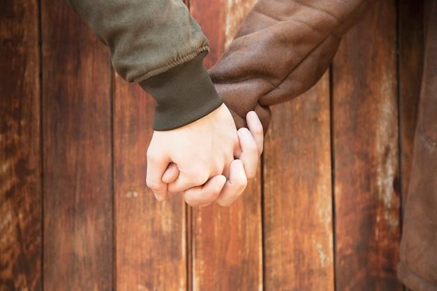 Crop men holding hands with love