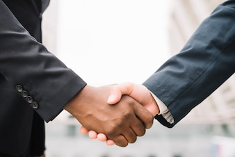 Crop men in suits shaking hands