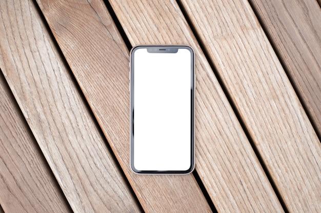 Обрезать макет изображения пустой белый экран сотовый телефон. фон пустое пространство для рекламного текста. современный мобильный телефон лежит на деревянной скамейке на столе из слоновой кости