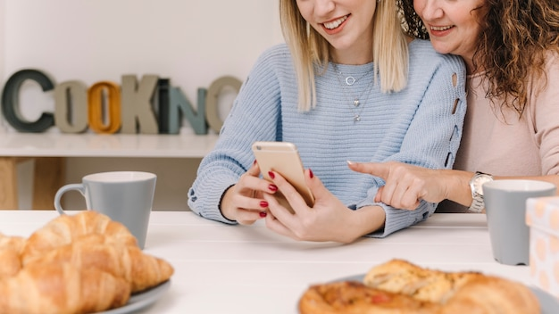 Crop mother and daughter using smartphone during breakfast
