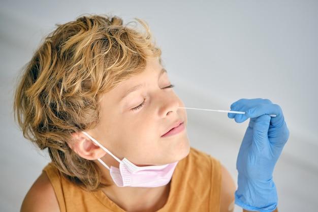 Медсестра принимает тест на covid у мальчика в клинике