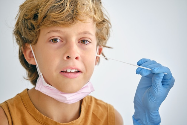 Медсестра с тампоном трогает лицо плачущего мальчика