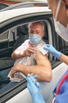 Медсестра с вакциной готовит пожилого пациента к прививке на открытом воздухе