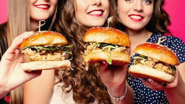 鶏肉と野菜のおいしいハンバーガーを保持している友人の作物。