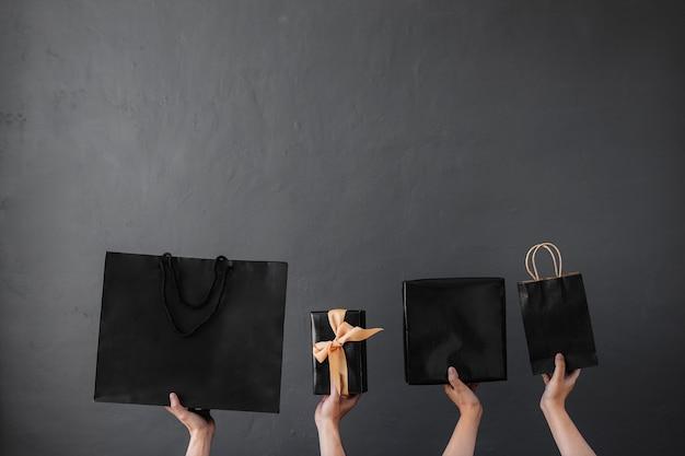 買い物中毒のオンラインショッピングの背景の概念のための買い物袋またはグッディバッグを持っている手の作物