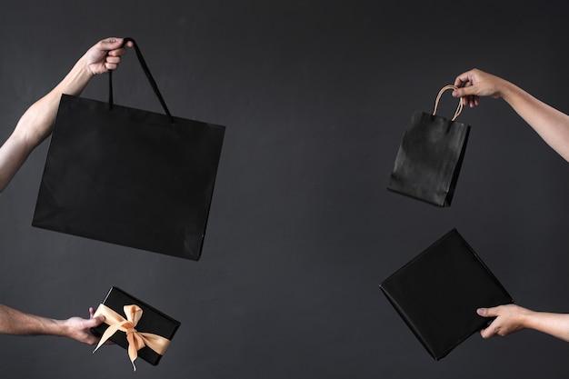 買い物中毒またはオンラインショッピングの背景のための買い物袋またはグッディーバッグを持っている手の作物