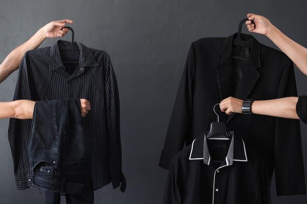 쇼핑 중독 및 검은 금요일 판매 판촉을 위해 검은 옷과 액세서리를 제공하는 손의 작물
