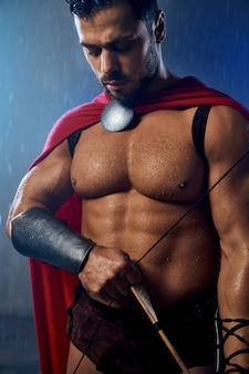 雨が降っている間、矢で弓を持って、赤いマントを身に着けている筋肉の大人のスパルタンの作物。悪天候で見下ろし、武器でポーズをとって歴史的な衣装で濡れたハンサムな白人男性のクローズアップ。
