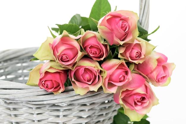 Урожай роз в корзине на белом фоне