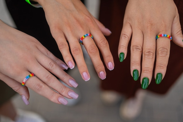 黒革のハンドバッグの差分に指を持ってスタイリッシュなマニキュアを見せている3人の女の子の作物...