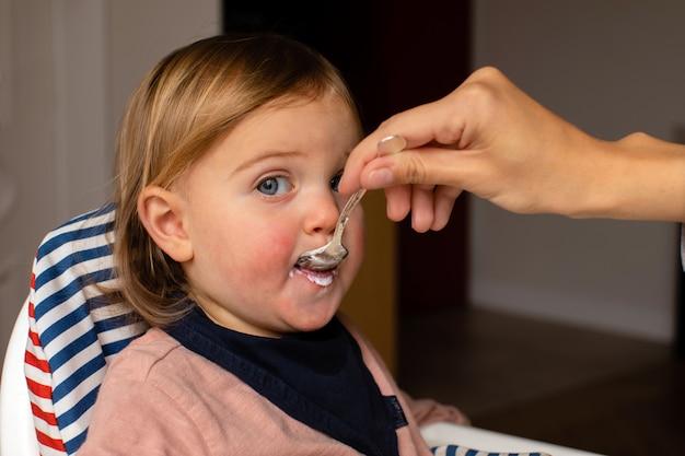 Crop parent feeding baby with porridge