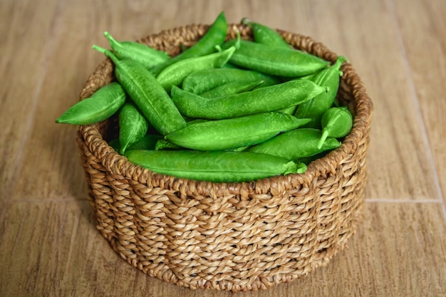 The crop of peas lies in a round wicker basket on a wooden background. central composition.