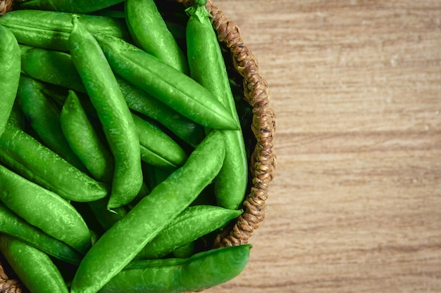 The crop of peas lies in a round wicker basket on a wooden background
