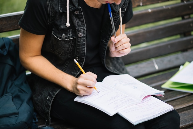 Crop pensive man studying on bench