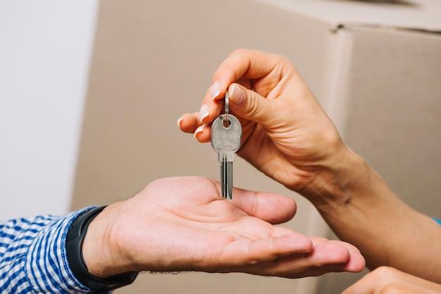 Crop people exchanging with keys