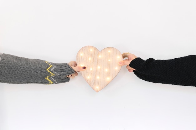 Crop people holding wooden heart