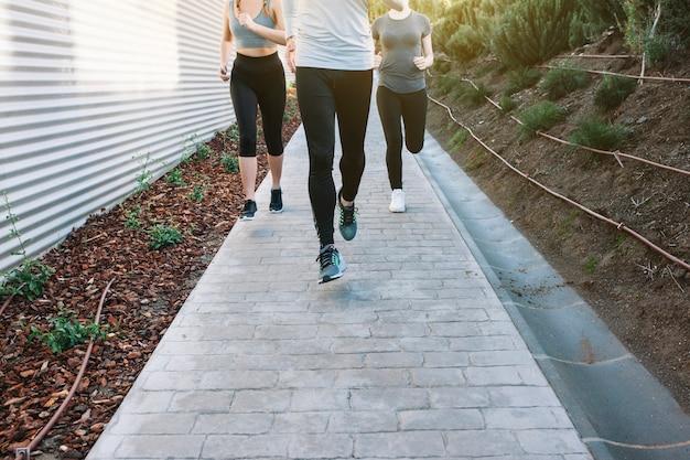 Crop people running on path