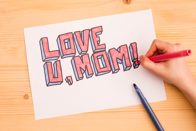 Crop person drawing inscription love u mom