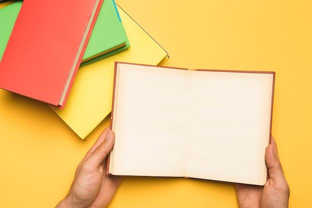 書籍のスタックの近くに開いているノートブックを保持している人をトリミングします。