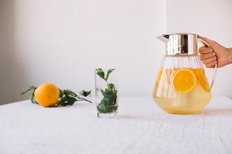 Crop person serving orange lemonade