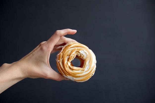 Урожай человек, показывающий пончик из заварного теста и зефира