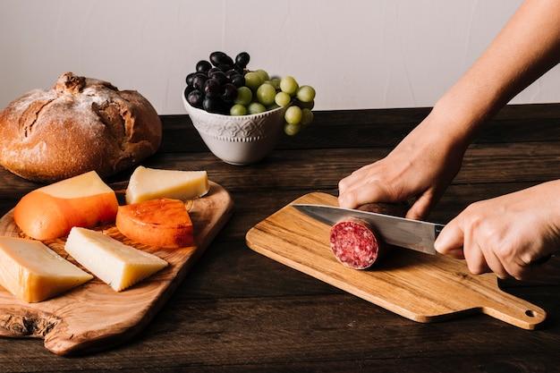 Crop person slicing sausage near food