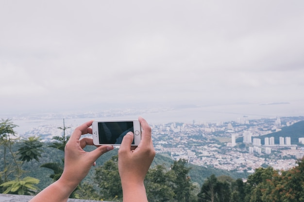 Crop person taking picture of cityscape