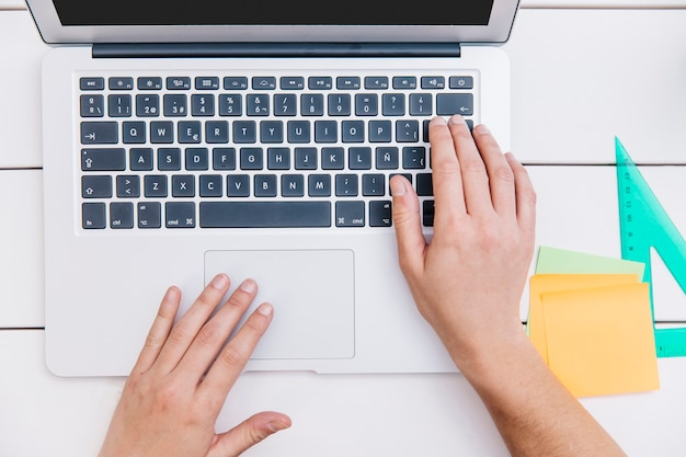 Crop person typing on laptop
