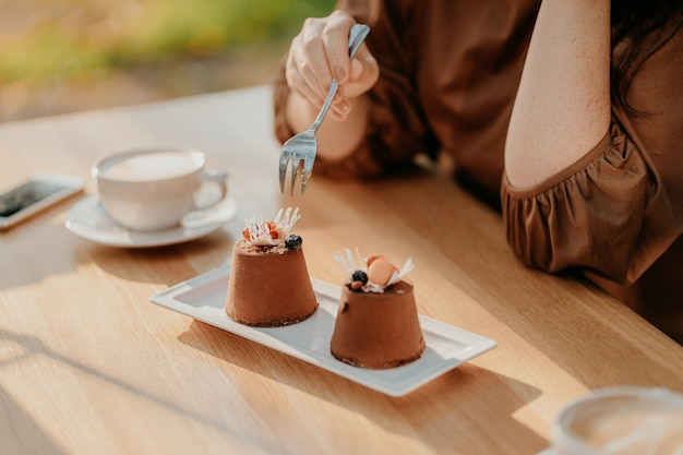 Crop photo of woman eating double tiramisu dessert decorated with fresh berries at cafe