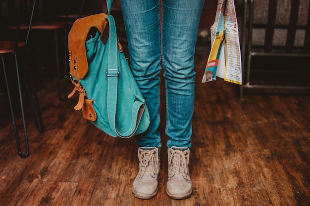 Crop photo of young woman feet girl traveler in jeans and boots with backpack and map indoors