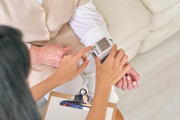 환자의 손목에 있는 안압계의 버튼을 누르는 의사 자르기
