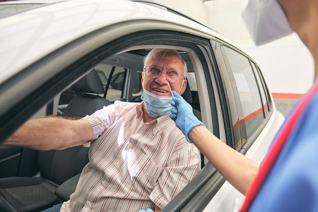Врач-растениевод с ватным тампоном против улыбающегося пациента в автомобиле