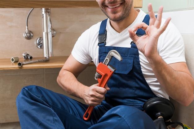 Crop plumber gesturing ok