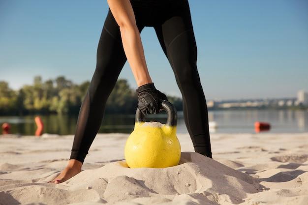 Ritaglia il ritratto di giovane donna che si allena con i pesi in spiaggia