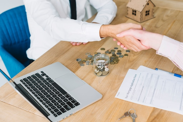 Crop real estate agent shaking hand of client