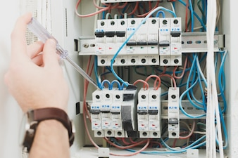 Crop repairman using screwdriver on switchboard