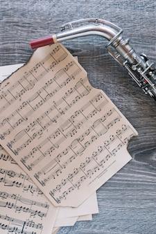 Crop saxophone near sheet music