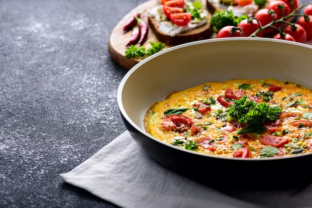 Crop scrambled eggs with tomatoes, spinach and pumpkin seeds in frying pan with toast with cottage cheese, pesto sauce, chili and cherry tomatoes on black background