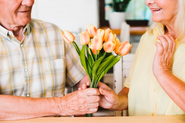 Crop senior man presenting bouquet to woman