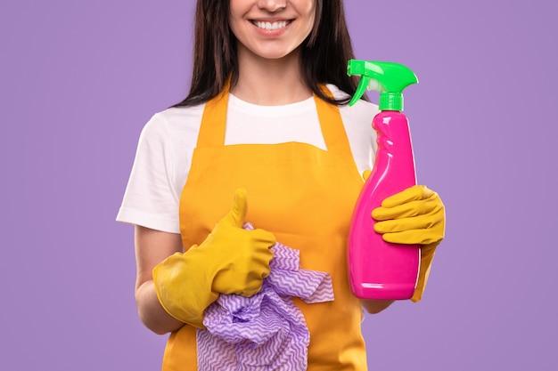 黄色いエプロンと手袋で笑顔の主婦を洗剤とナプキンでペットボトルを保持し、親指を立てるジェスチャーを示す