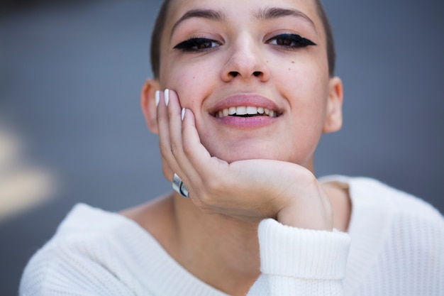Crop smiling woman holding chin and looking at camera